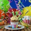 Cupcake with 11 candle surrounded by balloons and streamers.