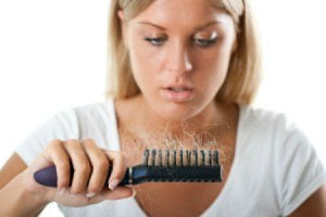 Woman looking at a brush full of hair.