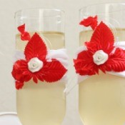 Two champagne flutes decorated with red and white flowers.