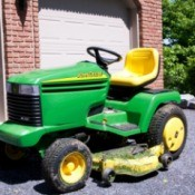 John Deere riding mower in a driveway.