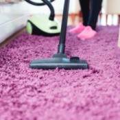 Vacuuming a purple rug.