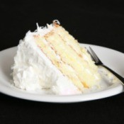 Slice of white layer cake on a plate.