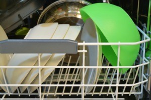 Green plastic bowl in a dishwasher.