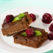 Pieces of fudge on a plate with cherries.