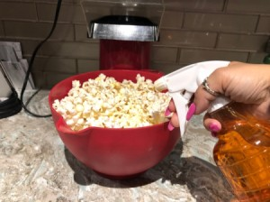 An oil spray being added to a bowl of popcorn.