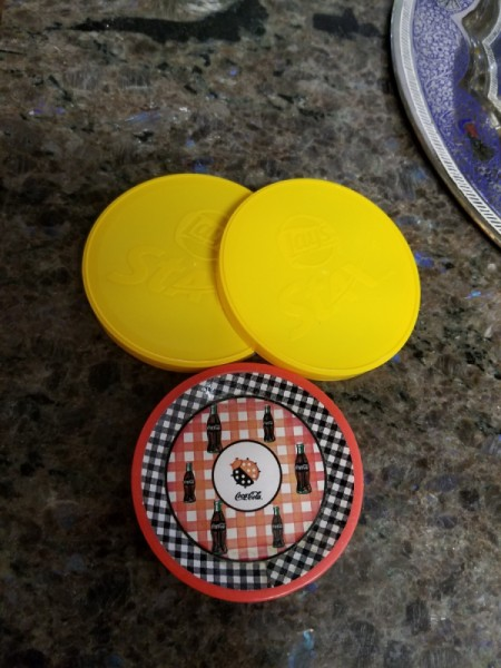 A round magnet next to two yellow round plastic lids.