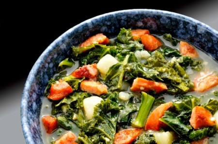 Kale soup with sausage and potato in a bowl.