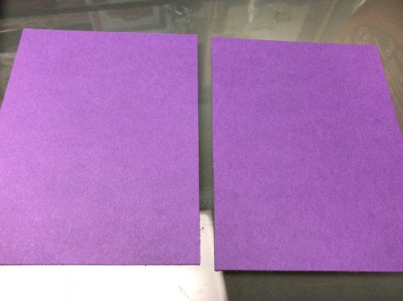 Two pieces of purple paper, to be used for a Halloween card.