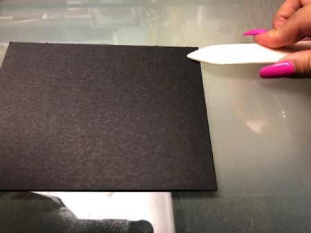 Folding a piece of cardstock to be the base of a card.