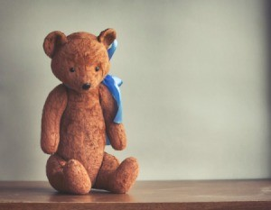 Stuffed teddy bear sitting on a table.