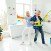 Grey Haired Couple ready to fight dust, man playing on mop like guitar, woman holding spray like gun and ready for shooting