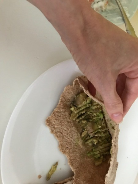 adding avocado to pita half