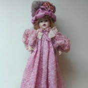 Identifying a Porcelain Doll - doll wearing deep pink long dress and fancy hat