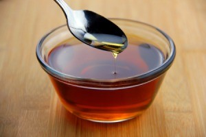 Bowl of syrup with a spoon.