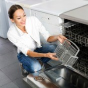 Woman looking at a dishwasher in a store.