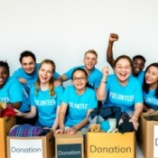 Group of volunteers in blue shirts with boxes of donations.
