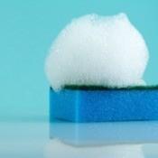 Blue sponge with soap foam on top.