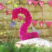 Number 2 party decoration covered in pink flowers.