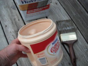 An easy to hold Coffee-mate plastic container with paint inside.