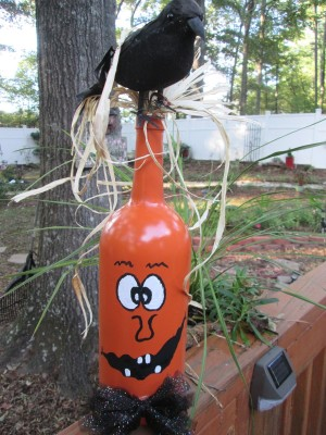 Jack-'o-Lantern Painted Wine Bottles - bottle painted, with raffia around the neck, hair and a bow tie