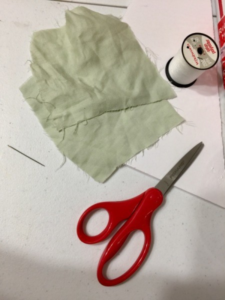 Soft fabric patches next to a pair of scissors and thread.