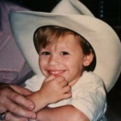 A small boy in a large white cowboy hat.