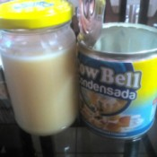 A can stored next to a jar fill of condensed milk.