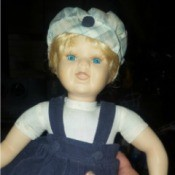 Value of a Porcelain Doll - doll wearing a blue jumper and plaid hat