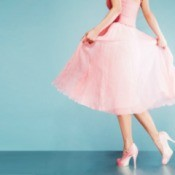 Woman in a pink prom dress with pink heels.