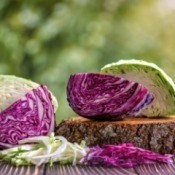 Cut Red and green cabbage on a table, outside.