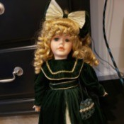 Value of a Collector's Choice Doll by Dandee - doll with gold ringlets, a large hair bow and a long dark coat