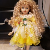 Value of a Cathay Depot Collection Doll = doll with long blond ringlets, wearing a bright yellow dress