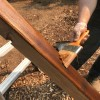 Restaining a wooden playground set  with a paintbrush.