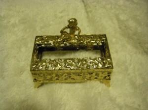 A vintage gold trinket on a white background.