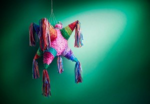 Piñata hanging in front of a green wall.