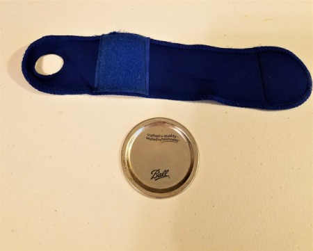 A wrist brace and a metal canning jar insert.