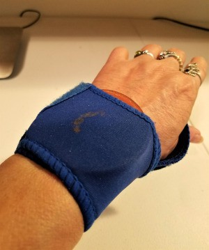 A wrist brace and a metal canning jar insert on a woman's wrist.
