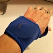 A wrist brace and a metal canning jar insert on a woman's wrist.