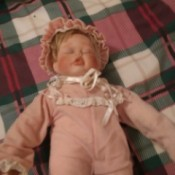 Value of Porcelain Dolls - sleeping baby doll in pink outfit