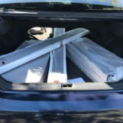 Shelving pieces removed from packaging and placed in a car's trunk.