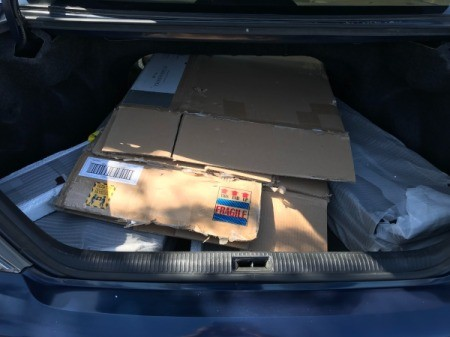 The flattened cardboard box on top of shelf pieces in a trunk.