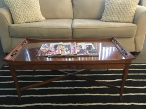 Value of a Glass Topped Vintage Coffee Table - table in front of a white couch