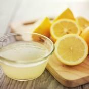 Bowl of lemon juice next to cut lemons.