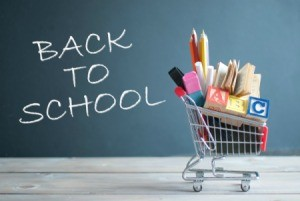 """Back to School"" written on a chalk board with a small shopping cart full of school supplies."