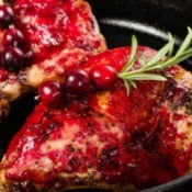 Berry glazed chicken with cranberry on rosemary garnish.