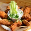 Fried chicken around a cup of ranch dressing with celery sticks.