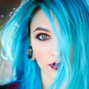Woman with blue hair and blue eyes.