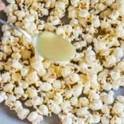 White chocolate being poured over popcorn.