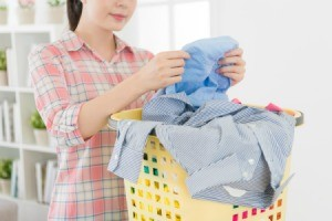 Woman looking at clothing in a laundry basket.