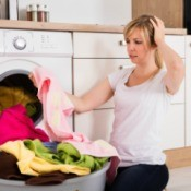 Woman looking at a towel turned pink in the wash.